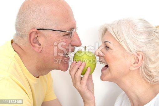 104545719istockphoto Senior couple with apple, healthy teeth concept 1141323459