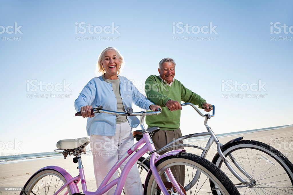 Senior couple with bicycles on beach royalty-free stock photo