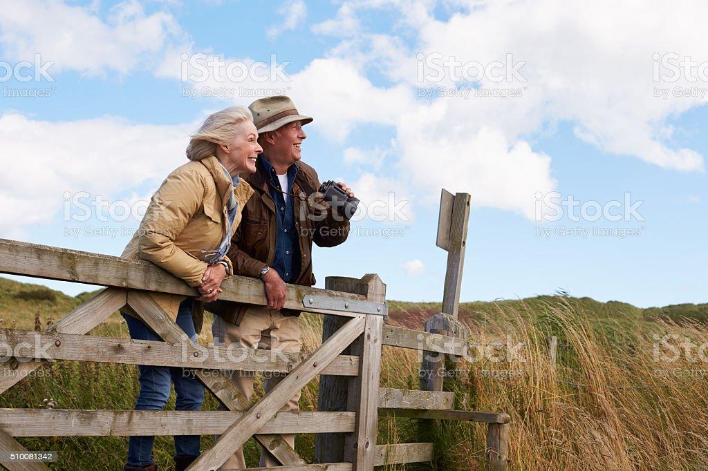 Altes Paar gehen In der Landschaft mit Fernglas – Foto