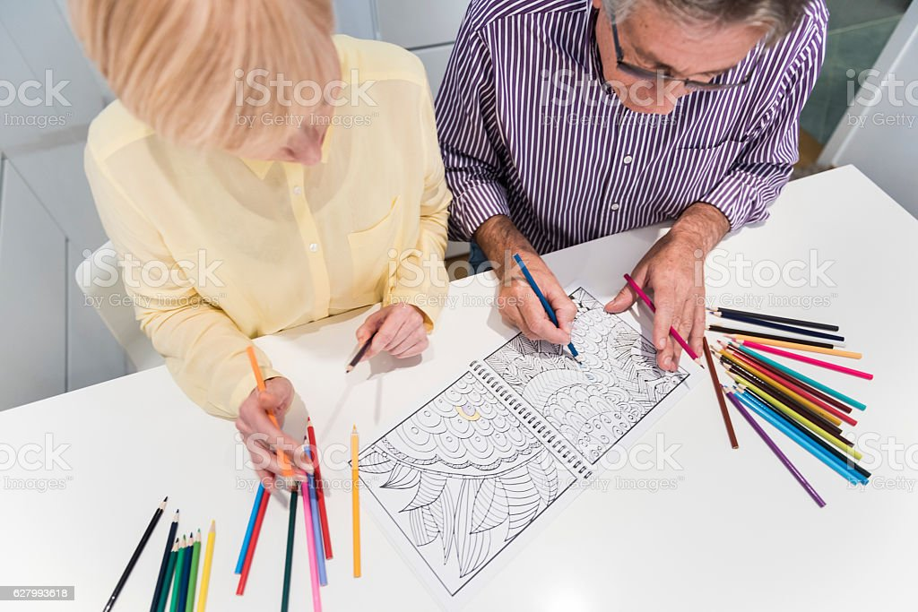 Senior couple with coloring book stock photo