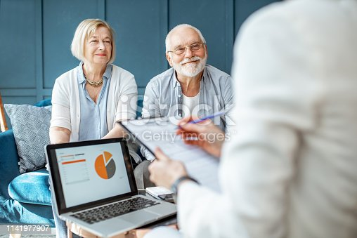 istock Senior couple with consultant at the office 1141977907