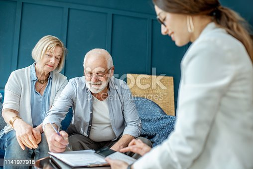 1129638619 istock photo Senior couple with consultant at the office 1141977918