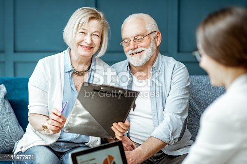 1129638619 istock photo Senior couple with consultant at the office 1141977971