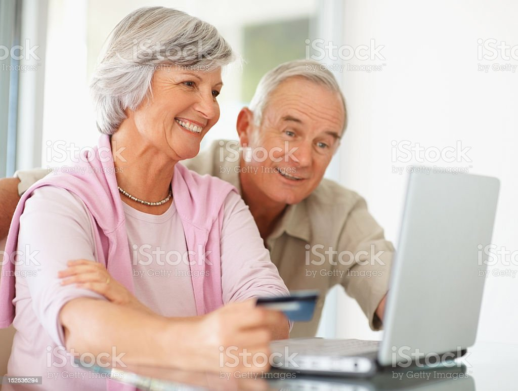 Senior couple with credit card shopping online on laptop royalty-free stock photo