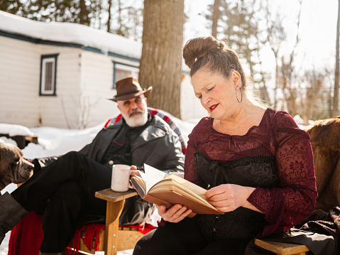 Canadian early retirement lifestyle: Senior couple  outdoors on the winter sun with their two dogs while enjoying hot beverage by the fire pit of their camping cottage.