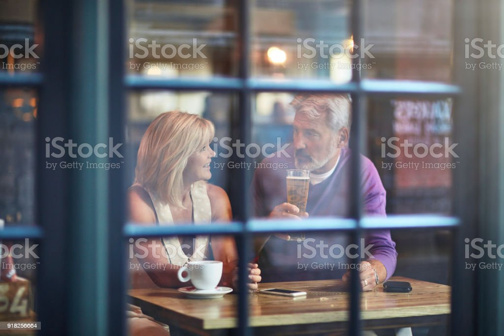 Senior couple with drinks seen from window - foto stock