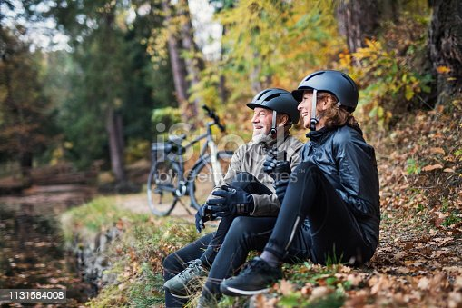 A senior couple with electrobikes sitting outdoors in park in autumn nature, resting.