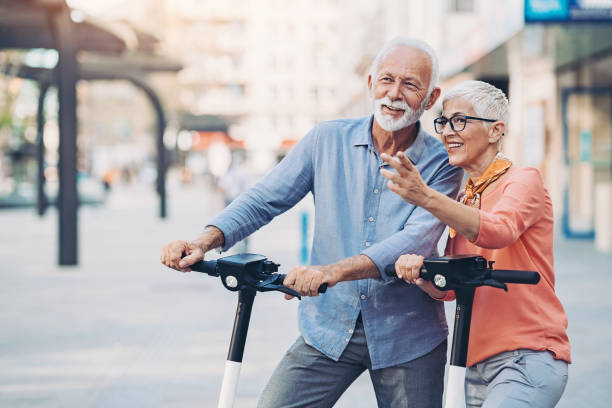 Senior couple with e-scooters stock photo