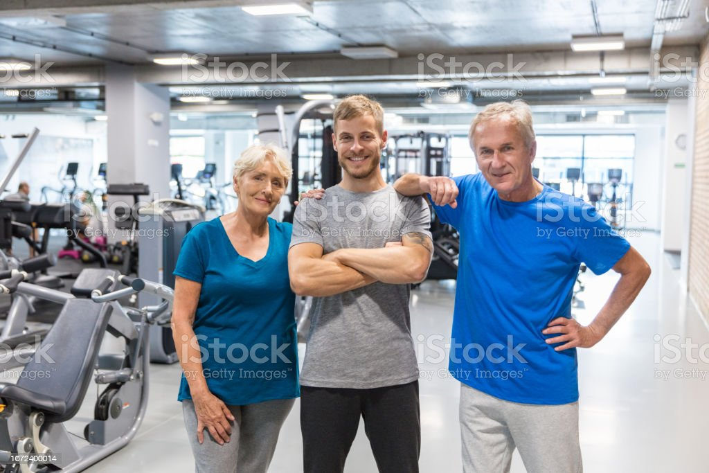 Senior man and woman with their trainer standing together at gym....