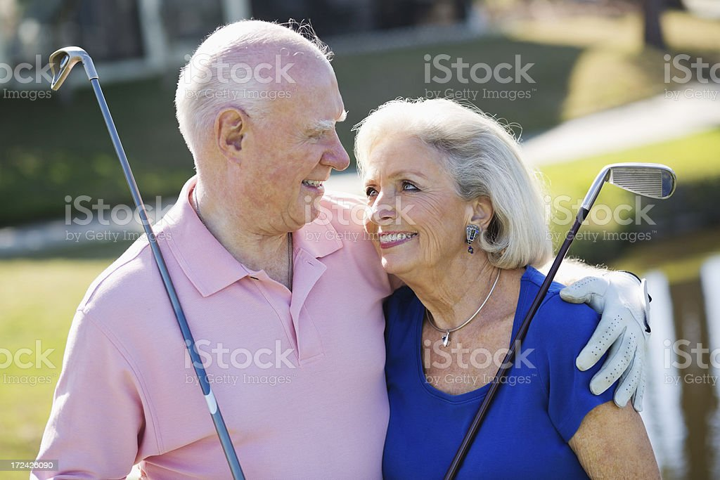 Senior Couple With Golf Clubs At Sports Venue royalty-free stock photo