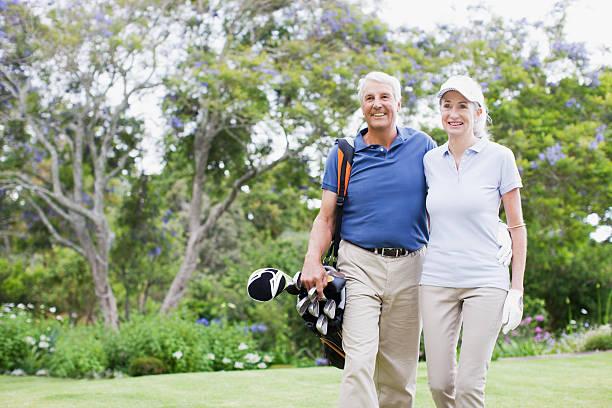 Senior couple with golf clubs stock photo