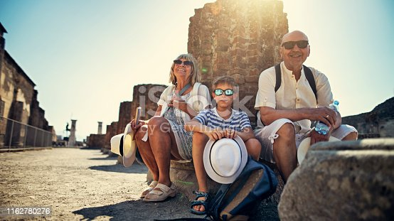 istock Senior couple with grandson sightseeing ancient ruins 1162780276