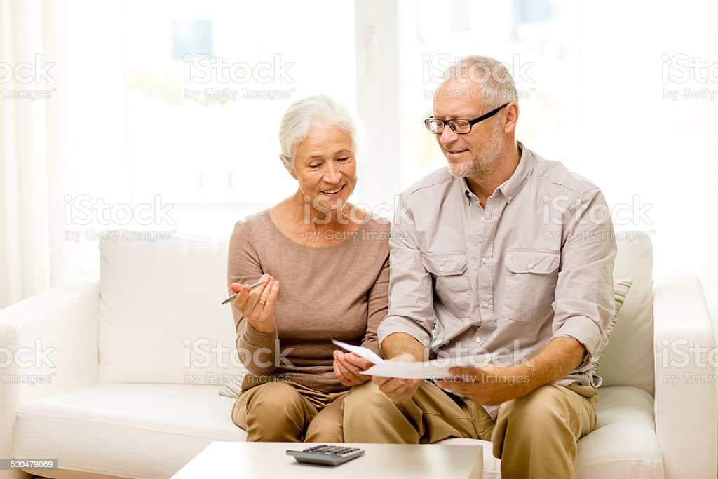 senior couple with papers and calculator at home stock photo