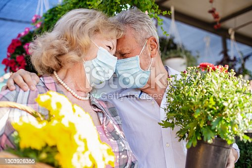 istock Senior couple with protective face masks on the market 1303926355