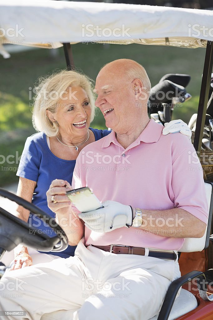 Senior Couple With Score Card In Golf Cart royalty-free stock photo
