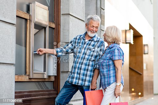 istock Senior couple with shopping bags using cash machine 1177096456