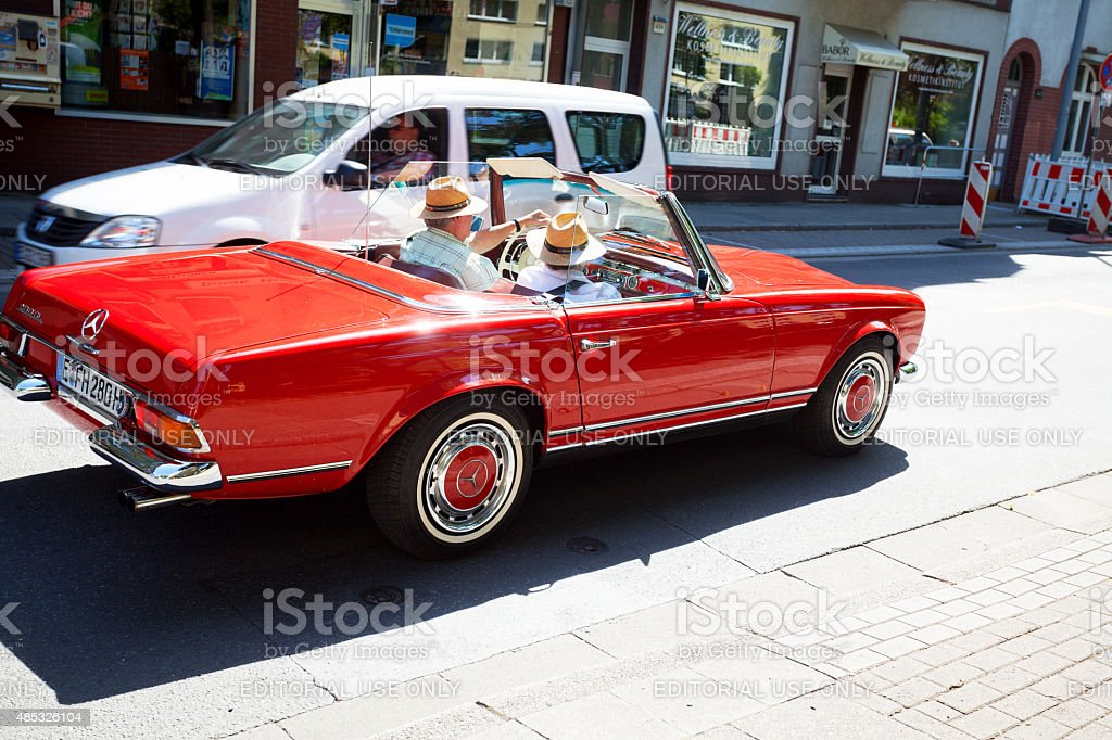 Senior couple with straw hats in red Mercedes SL stock photo
