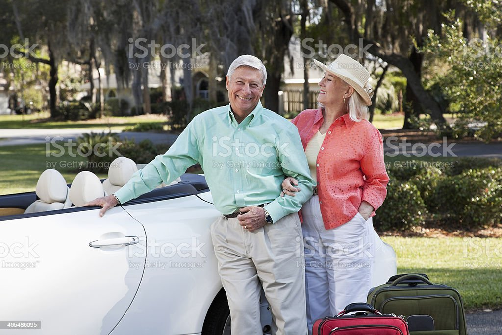 Senior couple with suitcases and convertible stock photo