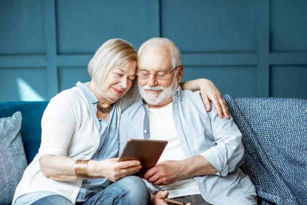 senior couple with tablet at home - grandparents foto e immagini stock