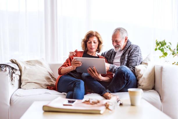 älteres paar mit tablet zu hause entspannen. - seniorenwohnungen stock-fotos und bilder