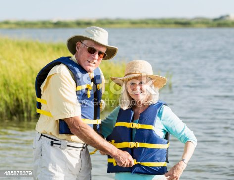 986720410 istock photo Senior couple with wearing life vests by water 485878379