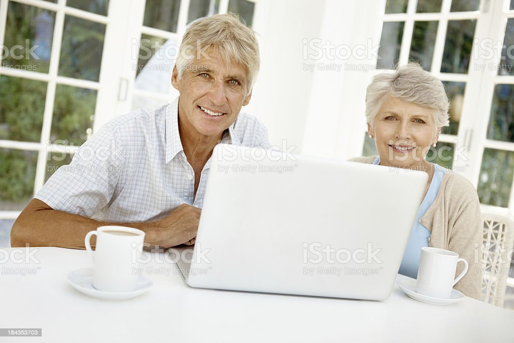 Senior couple working on laptop together stock photo