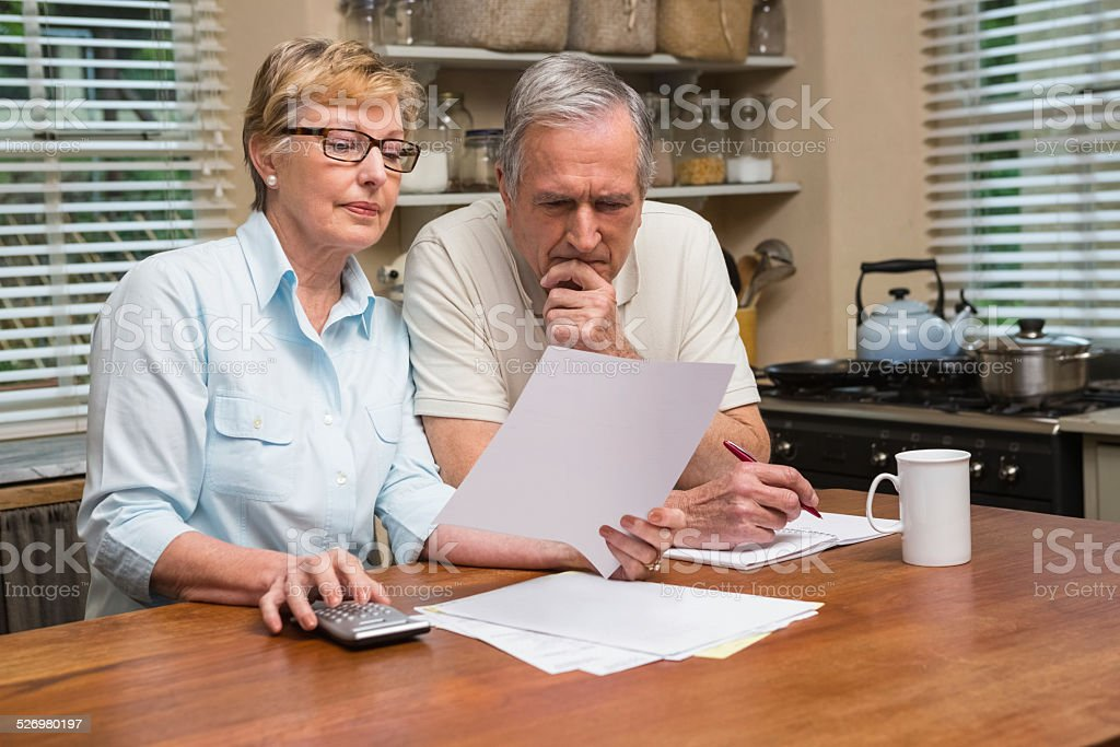 Senior couple working out their bills stock photo