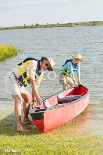 986720410 istock photo Senior couple working together to put canoe in water 463375693