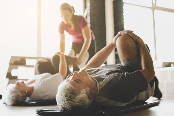 Senior couple workout in rehabilitation center. Personal trainer helps elderly couple to do stretching on the floor. Focus on man. stock photo