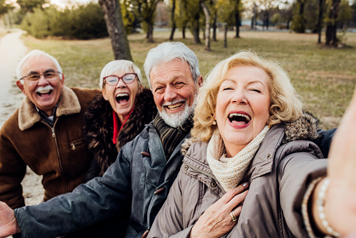 Senior couples laughing on a bench in a park
