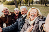 istock Senior couples laughing on a bench in a park 1072587056