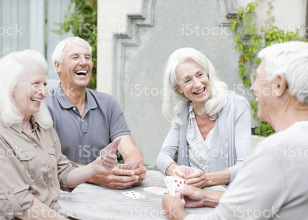 Senior couples playing cards on patio stock photo
