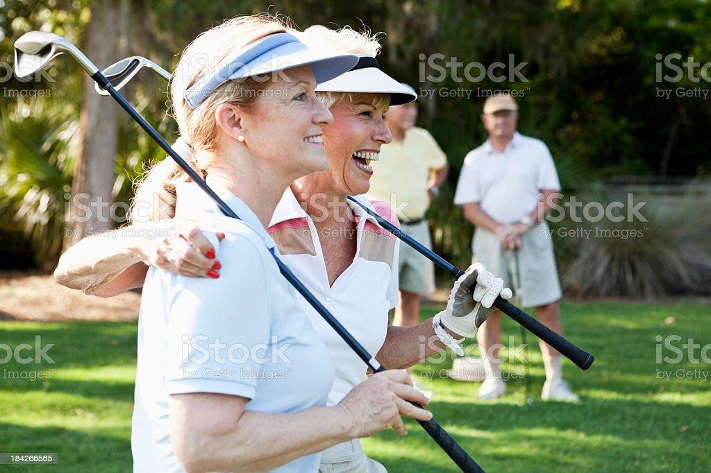 Senior couples playing golf. stock photo