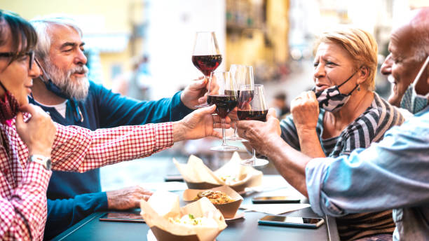 Senior couples toasting red wine at restaurant bar with face masks - New normal lifestyle concept with happy people having fun together at bar outdoors - Bright filter with focus on central glasses stock photo