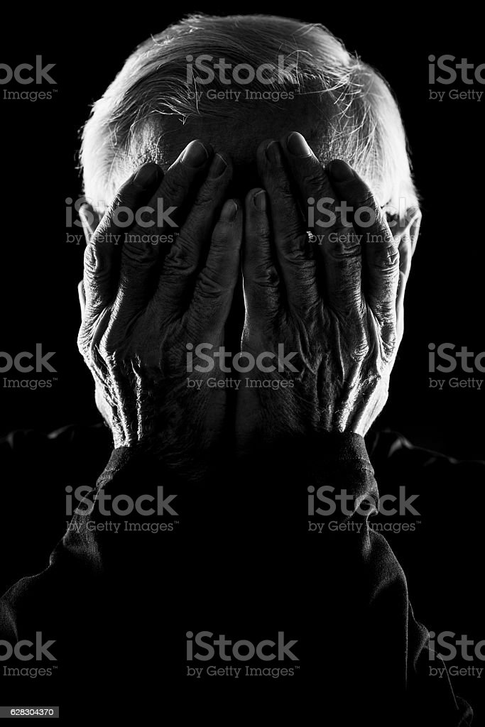 Senior covering face with hands stock photo