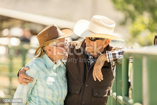 High Quality Stock photo of a husband and wife couple embracing and talking in an animal pen, horse riding area in Utah.