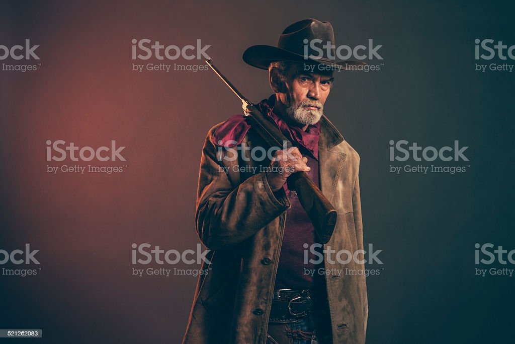 Senior cowboy with gray beard and brown hat holding rifle. stock photo