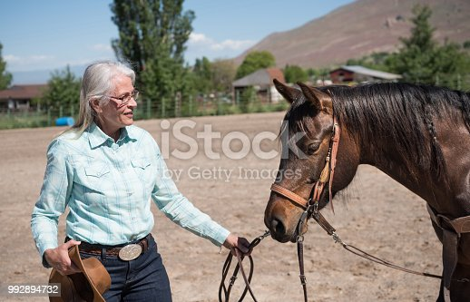 istock Senior cowgirl and her horse 992894732