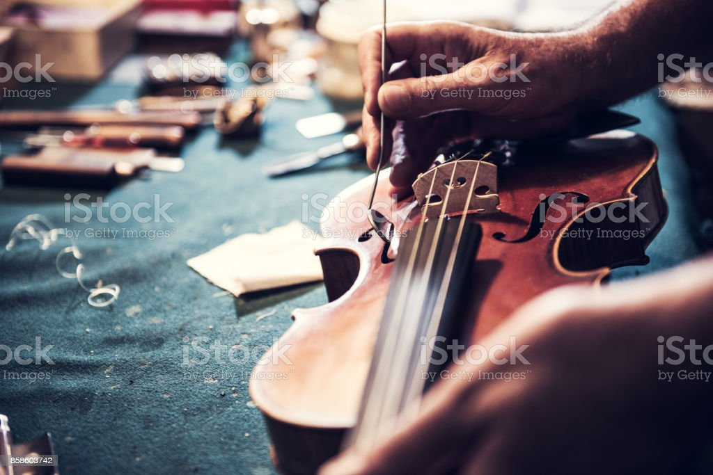 Senior craftsman checking the violin in his workshop stock photo