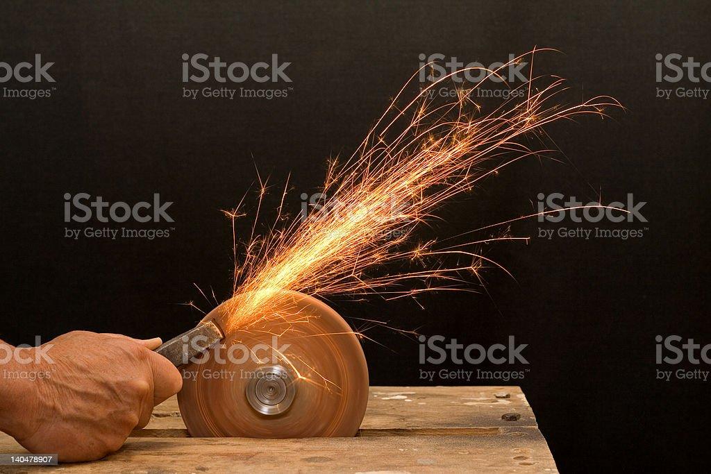 Senior craftsman hand grinding stock photo