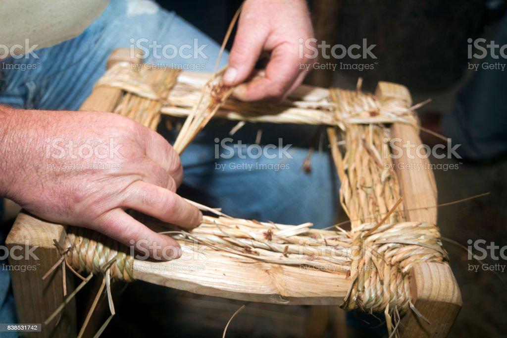 Senior craftsman weaving the seat of a stool. stock photo