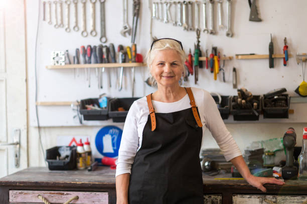 senior craftswoman in her workshop - pensionati lavoratori foto e immagini stock