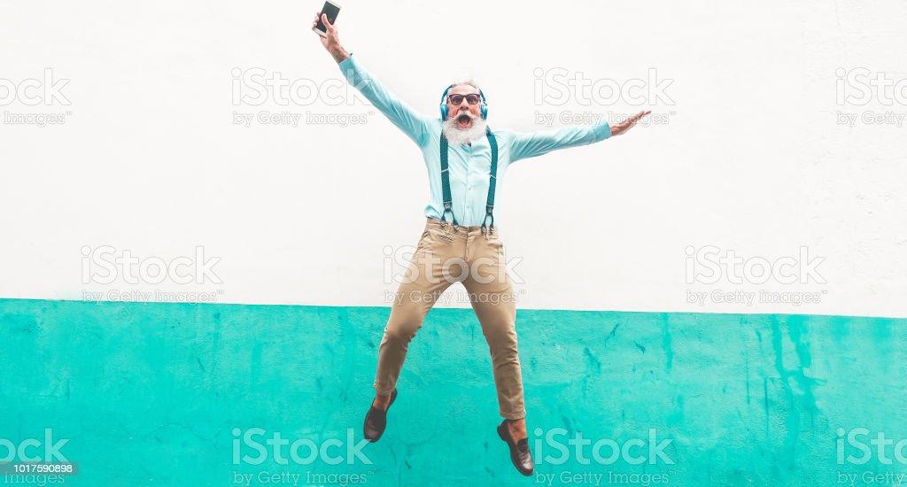 Homem louco sênior pulando e ouvindo música ao ar livre - macho maduro feliz celebrando e dançando fora - alegre idosos lifestyle conceito - foco nele foto de stock royalty-free