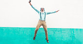 istock Senior crazy man jumping and listening music outdoor - Happy mature male celebrating and dancing outside - Joyful elderly lifestyle concept - Focus on him 1017590898