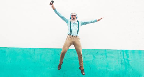 Homem louco sênior pulando e ouvindo música ao ar livre - macho maduro feliz celebrando e dançando fora - alegre idosos lifestyle conceito - foco nele - foto de acervo