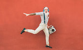 istock Senior crazy man jumping and listening music outdoor - Happy mature male celebrating and dancing outside - Joyful elderly lifestyle concept - Focus on him 1135963221