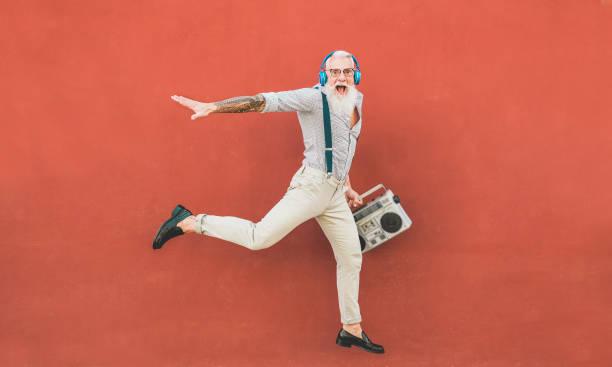 senior verrückte mann springen und hören musik im freien-happy reife mann feiern und tanzen draußen-freude ältere lifestyle-konzept-fokus auf ihn - alte tattoos stock-fotos und bilder