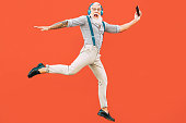 istock Senior crazy man jumping while listening music outdoor - Hipster male having fun dancing and celebrating life outside - Happiness, technology and elderly lifestyle people concept 1139469205