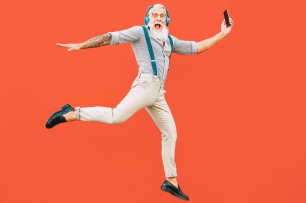senior crazy man jumping while listening music outdoor - hipster male having fun dancing and celebrating life outside - happiness, technology and elderly lifestyle people concept - eccentrico foto e immagini stock