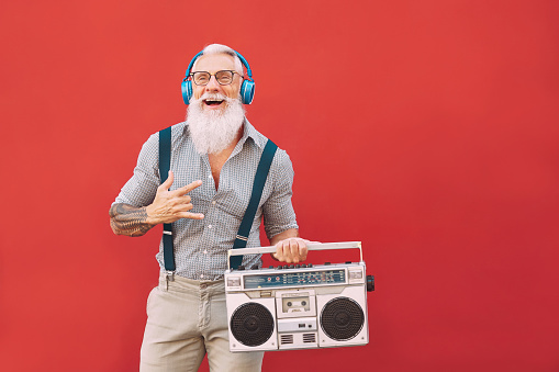 Senior crazy man listening music with headphones and vintage boombox outdoor - Hipster male having fun living in past time - Elderly people lifestyle activity - Red background